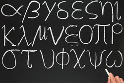 A-teacher-writing-the-Greek-alphabet-on-a-blackboard